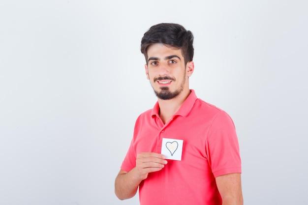 Giovane maschio che tiene una nota adesiva mentre distoglie lo sguardo in t-shirt e sembra felice, vista frontale.