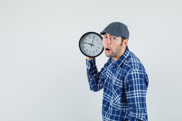 Молодой мужчина держит настенные часы в рубашке, кепке и выглядит удивленным, вид спереди.