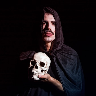 Young male in hooded cape holding skull