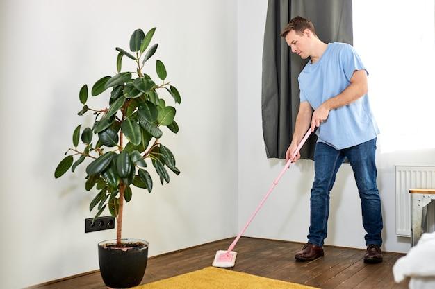 Молодой мужчина-домработница чистит пол, держа швабру на полу дома в гостиной, помогая своей жене, удаляя грязь и пыль, дома