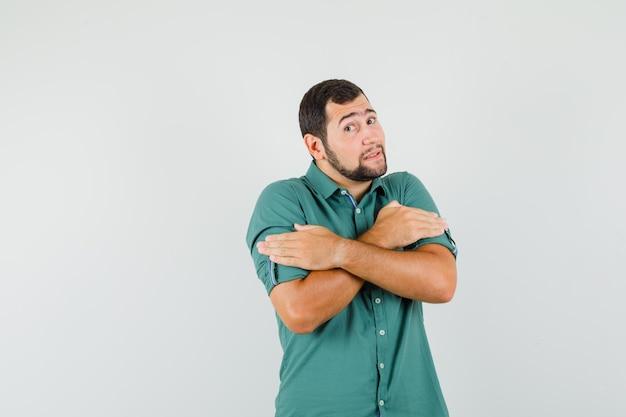 緑のシャツの正面図で寒くなりながら抱きしめる若い男性。