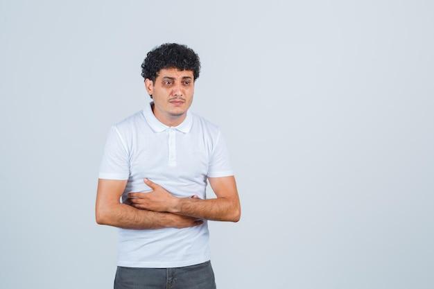 Giovane maschio che si abbraccia mentre pensa in maglietta bianca, pantaloni e sembra sconvolto, vista frontale.