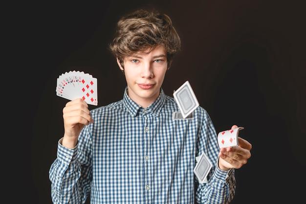 Молодой мужчина-иллюзионист бросить карту на темном фоне изолировал b