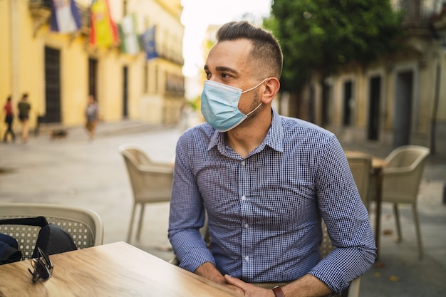 屋外カフェに座っている医療用フェイスマスクを身に着けている青いシャツを着た若い男性