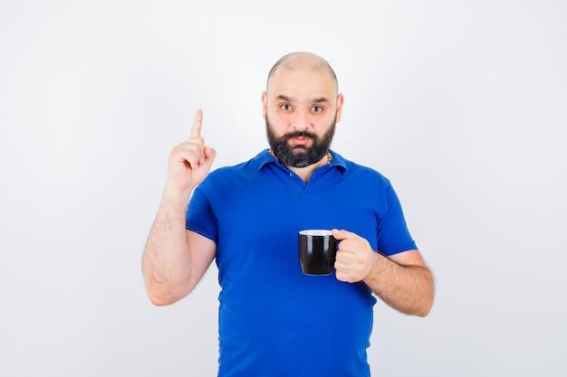 青いシャツを着た若い男性が上を向いて注意深く見ながらカップを保持し、正面図。
