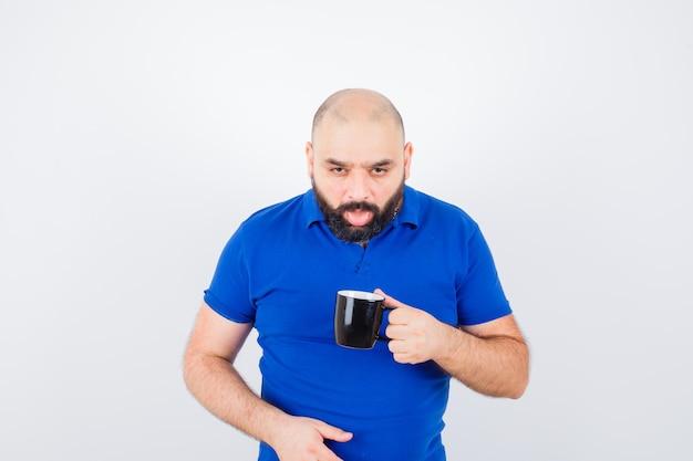 舌を突き出し、うんざりしているように見える間、カップを保持している青いシャツの若い男性、正面図。