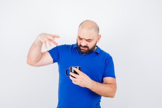 青いシャツを着た若い男性が手を上げてカップの中を見て、不満を見て、正面図。