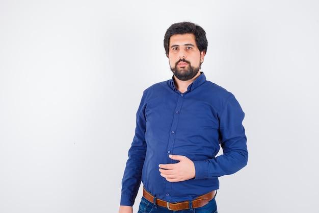 青いシャツを着た若い男性が立って、賢明な顔をしてポーズをとる、正面図。