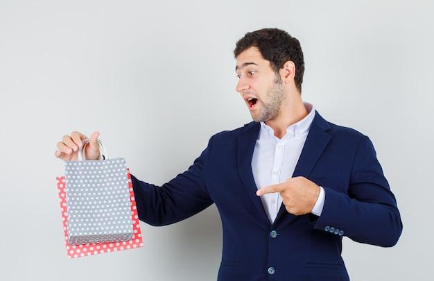 青いスーツを着た若い男性が紙袋を指差して驚いて見える正面図。