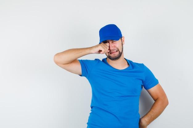 파란색 티셔츠와 모자에 어린 남성이 아이처럼 울고 우울해 보입니다.