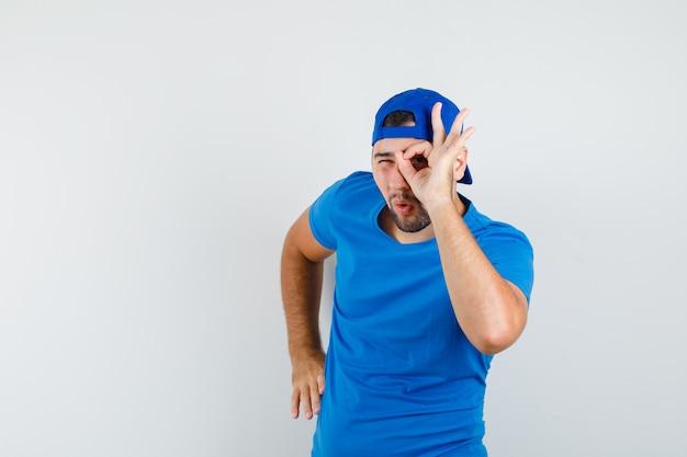 파란색 티셔츠와 모자에 눈에 ok 사인을 보이고 스누피를보고있는 젊은 남성
