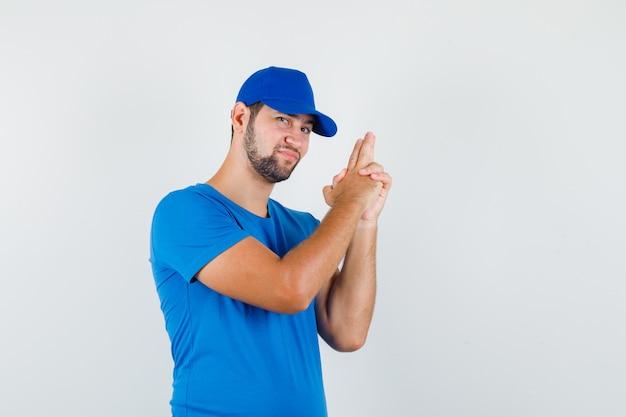Молодой мужчина в синей футболке и кепке показывает жест стрельбы и улыбается