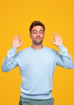 Молодой мужчина в повседневной одежде закрывает глаза и жестикулирует гиан мудру во время медитации на желтом фоне