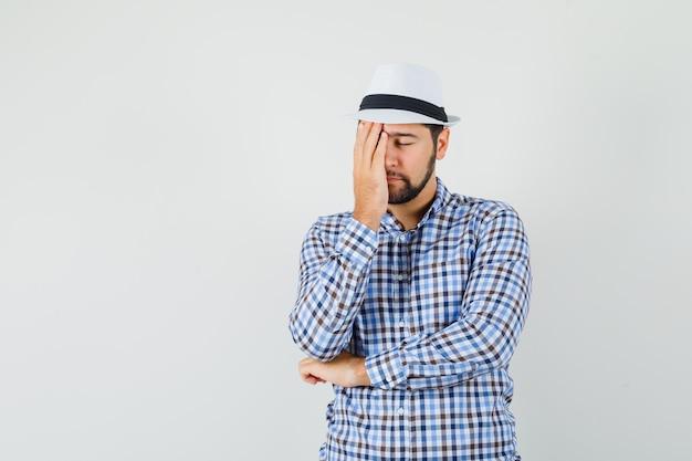체크 셔츠에 젊은 남성, 모자 얼굴에 손을 잡고 고 지쳐, 전면보기.