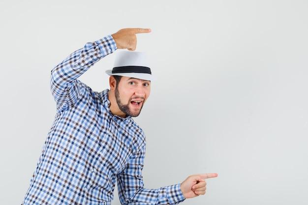 체크 셔츠, 모자 측면을 가리키고 호기심, 전면보기를 찾고있는 젊은 남성.