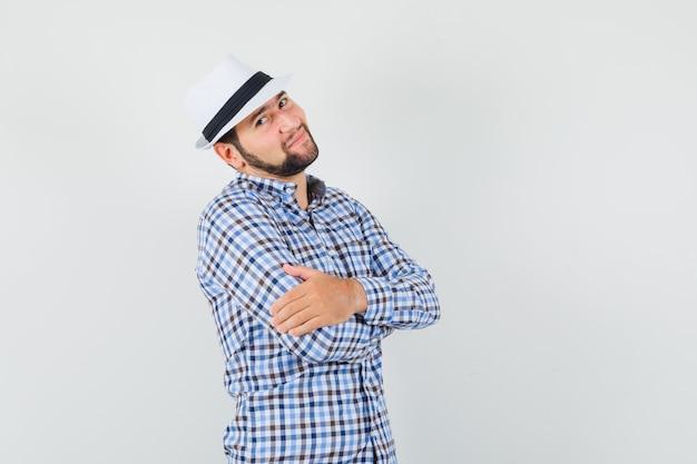 Молодой мужчина в клетчатой рубашке, шляпе, стоящей со скрещенными руками и симпатичной, вид спереди.