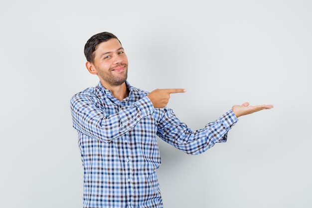 Молодой мужчина в клетчатой рубашке показывает на свою разложенную ладонь и выглядит весело