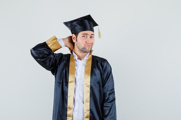 首に手を握り、エレガントな正面図を探している大学院の制服を着た若い男性。