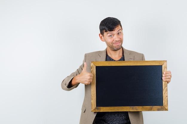 회색 갈색 재킷에 젊은 남성, 엄지 손가락을 보여주는 동안 골판지를 들고 검은 셔츠 기쁘게, 전면보기.