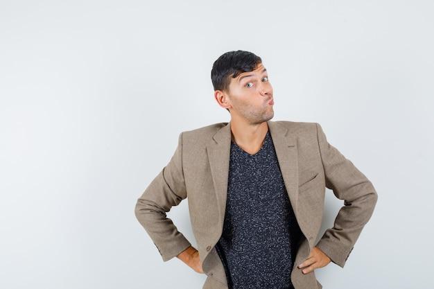 灰色がかった茶色のジャケットを着た若い男性、ふくれっ面の唇で立っている黒いシャツ、奇妙に見える、正面図。
