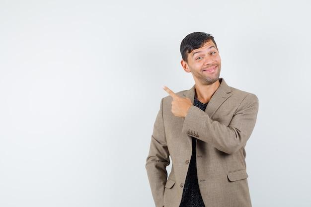 Молодой мужчина в серовато-коричневой куртке, указывая назад и глядя весело, вид спереди.