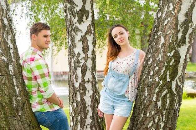 녹색과 빨간색 격자 무늬 셔츠를 입은 젊은 남성과 분수와 다른 나무가 있는 공원에서 나무에 기대어 카메라를 바라보는 여성