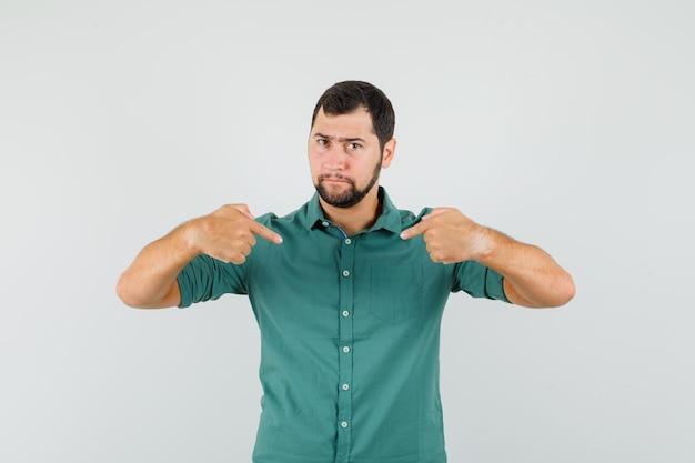 Молодой мужчина в зеленой рубашке, указывая на себя и глядя внимательно, вид спереди.