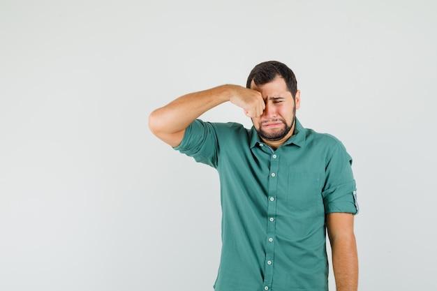 녹색 셔츠를 입은 젊은 남성이 울면서 화를 내는 동안 눈을 비비며 정면을 바라보고 있습니다.