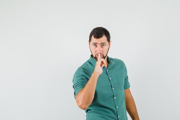 沈黙のジェスチャーを示し、集中して見える緑色のシャツを着た若い男性、正面図。