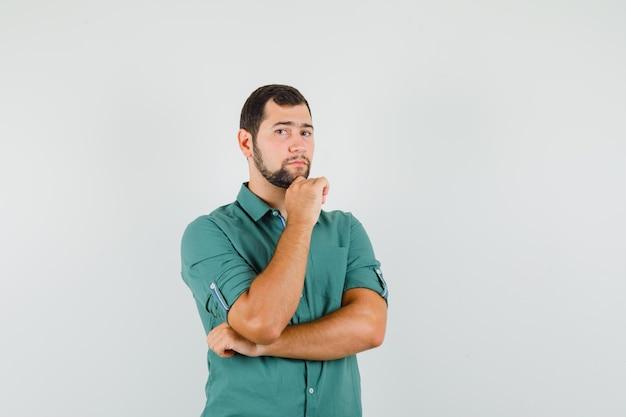Молодой мужчина в зеленой рубашке стоял и выглядел внимательным, вид спереди.