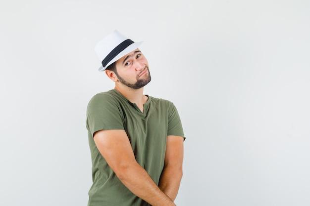 녹색 티셔츠와 모자 카메라를보고 당황한 젊은 남성