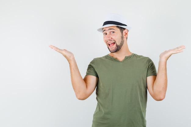 Молодой мужчина в зеленой футболке и шляпе делает жест весы и выглядит веселым