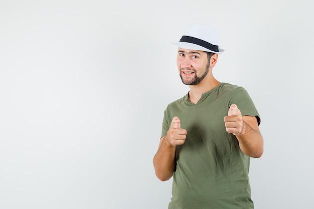 녹색 t- 셔츠와 모자 카메라를 가리키고 자신감을 찾고있는 젊은 남성