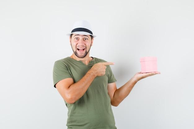 緑のtシャツと帽子の若い男性がギフトボックスを指して、陽気に見える
