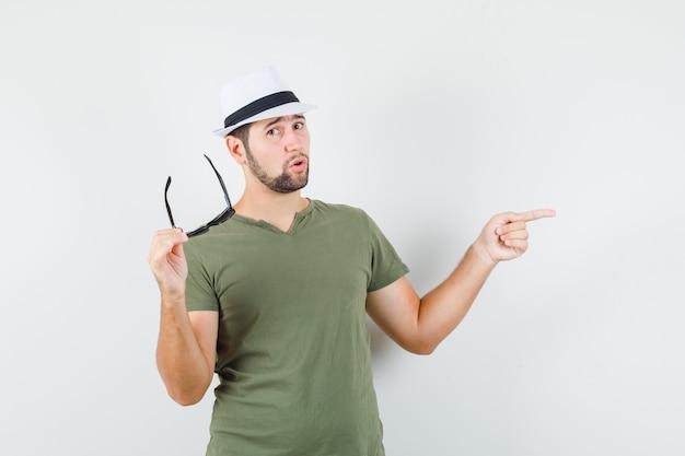 녹색 티셔츠와 모자에 젊은 남성이 안경을 들고 시원하게 보이는 동안 멀리 가리키는