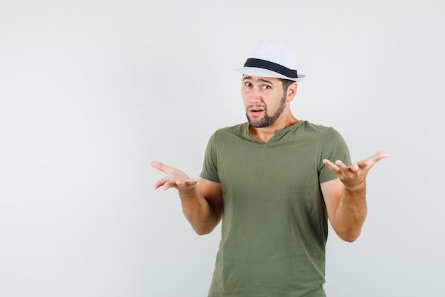 Молодой мужчина в зеленой футболке и шляпе вопросительно поднимает руки и выглядит смущенным