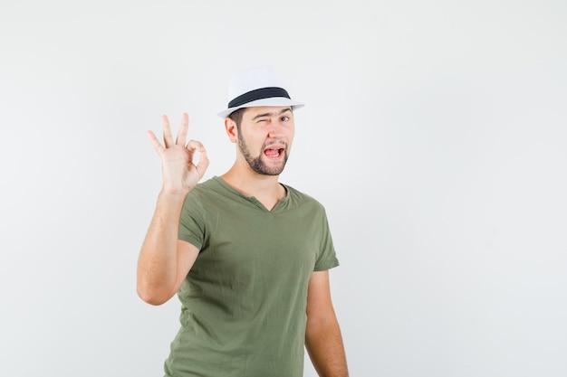 Молодой мужчина в зеленой футболке и шляпе показывает знак ок и подмигивает