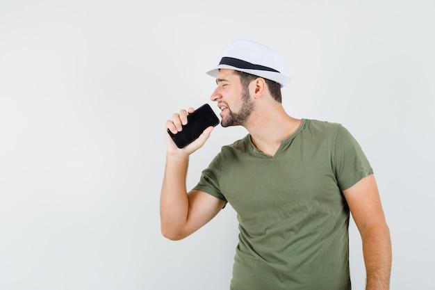 Молодой мужчина в зеленой футболке и шляпе поет в мобильный телефон как микрофон и выглядит резво