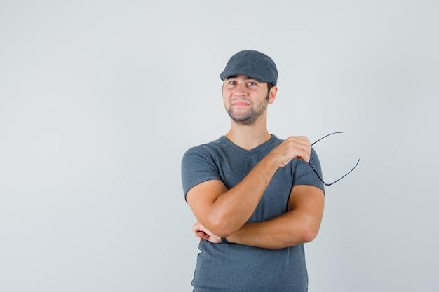 メガネを保持し、自信を持って見える灰色のtシャツキャップの若い男性