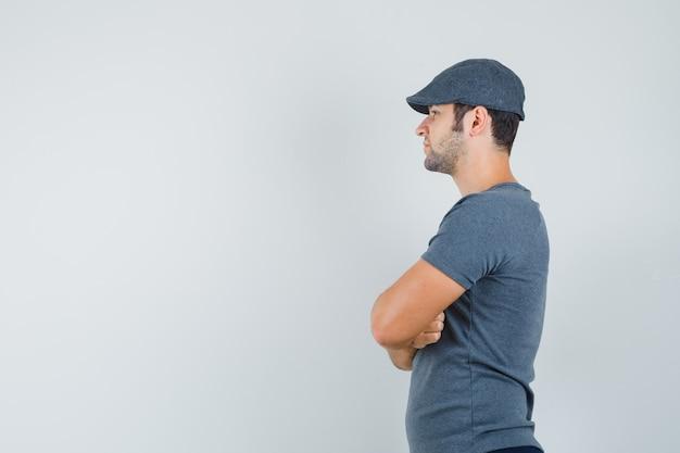 회색 티셔츠에 젊은 남성, 교차 팔으로 서서 자신감을 찾고 모자.