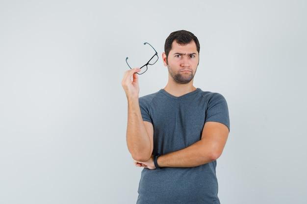 眼鏡をかけ、躊躇している灰色のtシャツの若い男性
