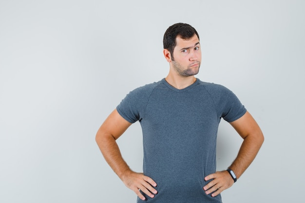 腰に手をつないで躊躇している灰色のtシャツの若い男性