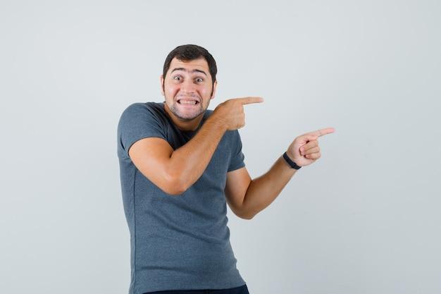 右側を指して、うれしそうに見える灰色のtシャツの若い男性