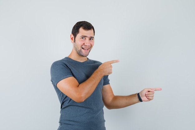 横を向いて陽気に見える灰色のtシャツの若い男性