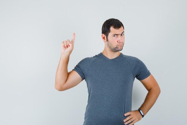 Молодой мужчина в серой футболке указывает вверх и выглядит серьезным