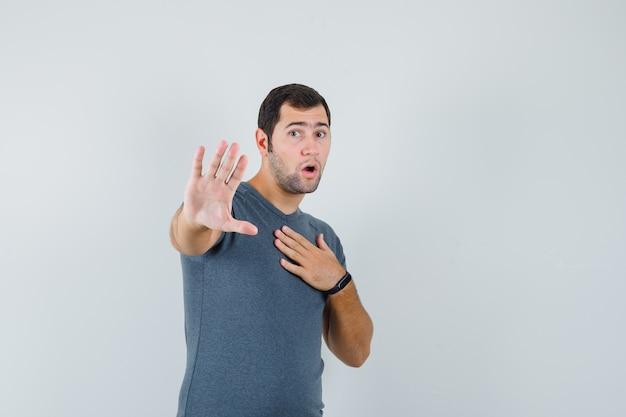 停止ジェスチャーを示し、怖がって見える灰色のtシャツの若い男性