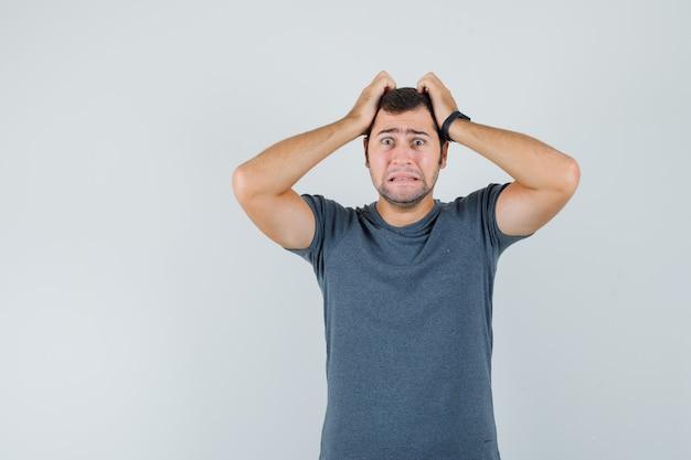 Молодой мужчина в серой футболке рвет волосы и выглядит беспомощным