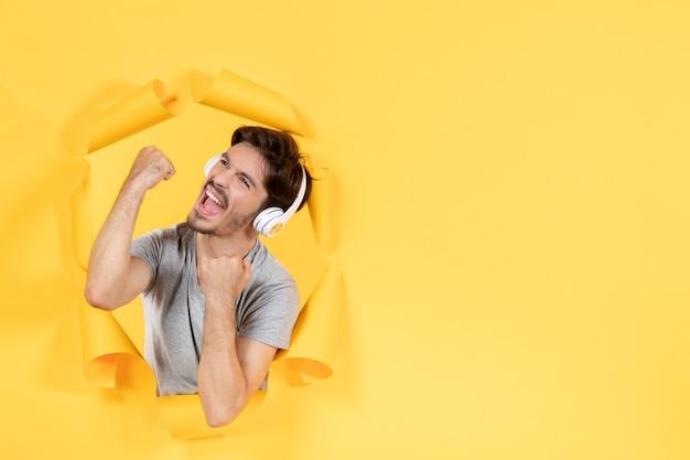 찢어진 노란 종이 배경 초음파 오디오 사운드에 헤드폰을 끼고 있는 젊은 남성