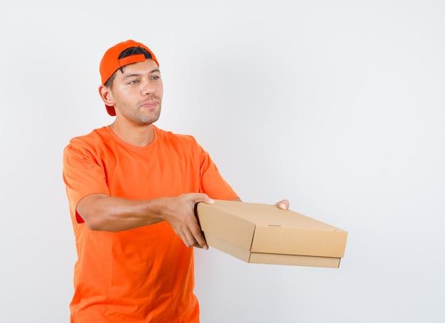 オレンジ色のtシャツとキャップの若い男性が段ボール箱を配達し、責任を探しています