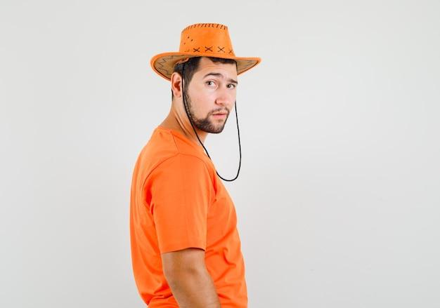 オレンジ色のtシャツ、帽子、賢明に見える若い男性。